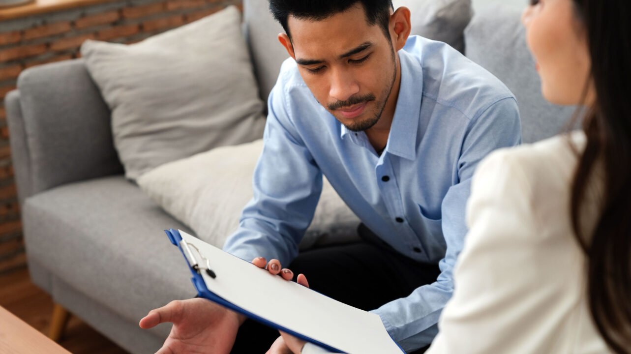 woman holding clipboard talking to man sitting on couch