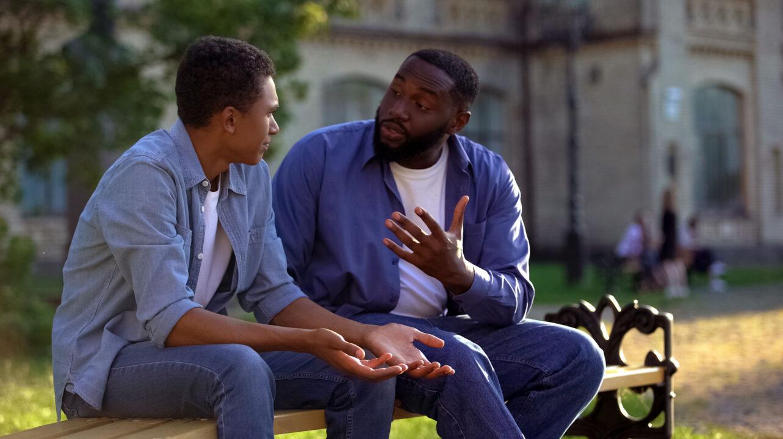 image of two men talking sitting on park bench